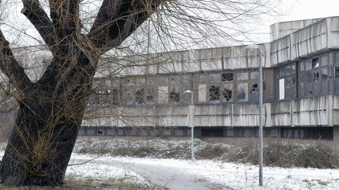 Das Bild zeigt ein verlassenes Gebäude aus dreckigem Sichtbeton mit zerschlagenen Fensterfronten. Vor dem Gebäude steht ein Baum ohne Blätter. Ein Weg vor dem Gebäude und Büssche die von etwas Schnee bedeckt sind.