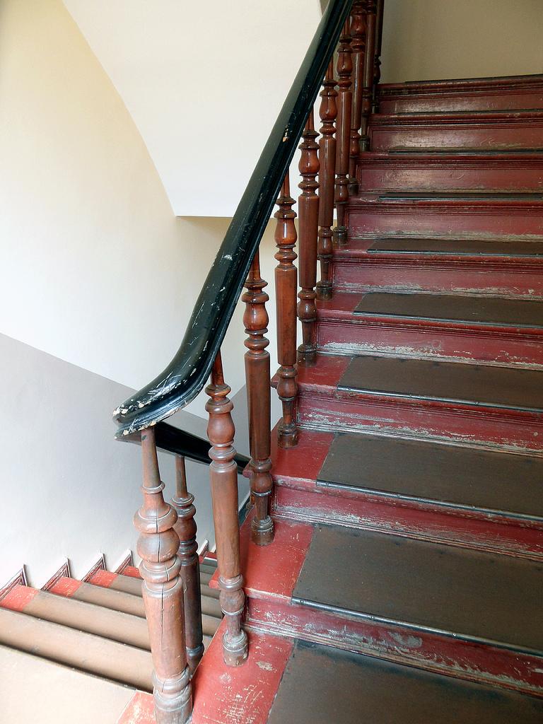Das Bild zeigt ein altes Treppenhaus mit abgetretenen roten Stufen und einem Holzgeländer.
